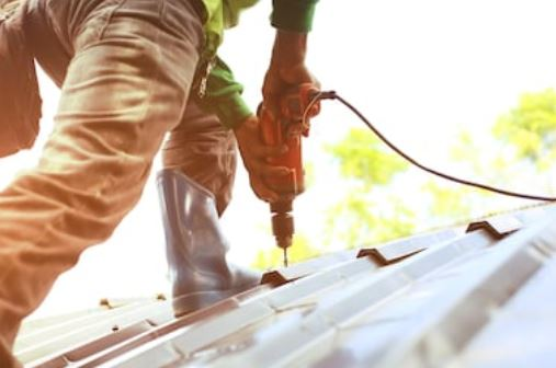 working drilling on a roof